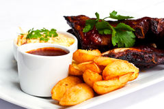 Marinated spareribs and fries. On a plate Stock Images
