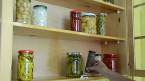 Marinated vegetable jar. Housewife puts on the shelves a variety of canned marinated vegetables in glass jars stock video