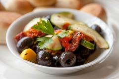 Marinated vegetables: olives, zucchini, tomatoes with yeast buns stock photos