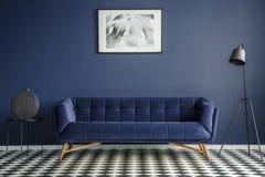 Marinblå ruminre med den bekväma flotta soffan i midden royaltyfria foton