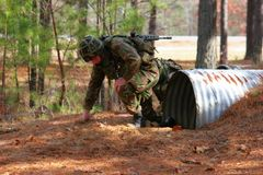 Marine on assault course. A Royal Marine emerges from a tunnel while on an assault course royalty free stock photo