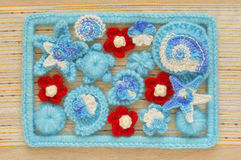 Marine background with cotton lace crochet craft elements: stars, shells, flowers and frame made of soft acrylic like wool yarn. C Stock Photography