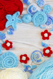 Marine background with cotton lace crochet craft elements: stars, shells, flowers and frame made of soft acrylic like wool yarn. C Stock Images