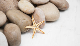 Marine background with pebbles and starfish Royalty Free Stock Images