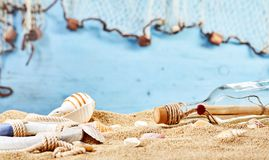 Marine beach still life with mystery letter. In a bottle washed up on golden sand scattered with seashells and a life ring over blue with copy space Stock Images