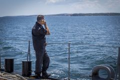 Marine black camouflage officer and boots hold a radio station on the deck of a warship in the Black Sea/Bulgaria/07.19.2018/ stock image
