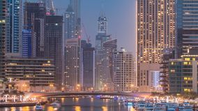 Evening Dubai marina city centre with floating vessels day to night timelapse. Marine boat interchange with view on Dubai marina illuminated city centre in stock video