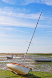 Marine boat with a mast after high tide in the bay. Royalty Free Stock Photos