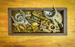 Marine Brightwork and Brass Spares. Metal boat parts including brass cleats, shackle, pulleys, screws, oar locks and more in a worn, well-used wooden box on a Royalty Free Stock Photos