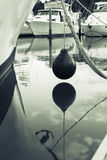 Marine buoy hanging above water between moored boats in Tutukaka Royalty Free Stock Images