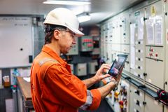 Marine chief engineer watching digital tablet in engine control room royalty free stock photography