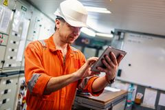 Marine chief engineer watching digital tablet in engine control room stock photo