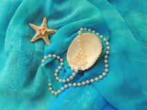 Marine composition in turquoise textile. Sea shell composition with the pearl thread and a starfish on turquoise fabric pareo Stock Photos