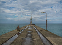 Marine concrete pier with crane. Cloudy sea Royalty Free Stock Images