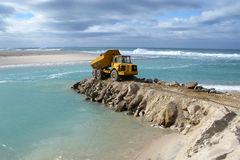 Marine construction. truck dumping rocks at sea. Marine construction - A big yellow truck dumping heavy rocks in to the currents of an estuary inlet, to build a Stock Photos