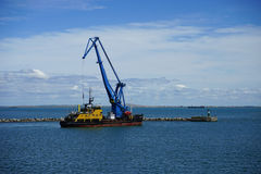 Marine crane in the Kerch Strait is engaged in the construction. Marine crane engaged in their work against the background of blue sea Royalty Free Stock Photo
