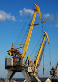 Marine cranes closeup. Marine cranes in the port closeup to the background of blue sky with clouds stock photo