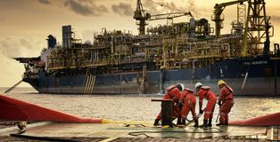 Marine crew work at aft deck during evening. Marine crew busy pulling wire rope during anchor handling operation at sea beside floating production storage oil Stock Photography