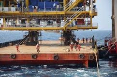 Marine crews work on mooring ropes. Marine crews pull mooring ropes to secure platform topside barge to heavy lift vessel stock photo