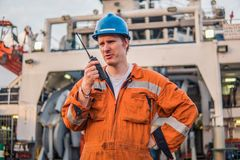 Marine Deck Officer or Chief mate on deck of ship with VHF radio Stock Image