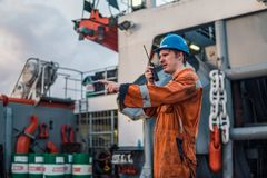 Marine Deck Officer or Chief mate on deck of ship with VHF radio Stock Images