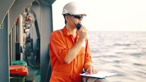 Deck Officer on deck of offshore vessel holds VHF walkie-talkie radio