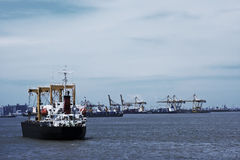 Marine docks. Transport ship on sea, cranes and harbor in background Royalty Free Stock Image