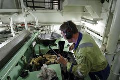Marine Engineer changing a Diesel Fuel Injector. A ships engineer carrying out routine maintenance on one of the main propulsion engines in port Stock Images