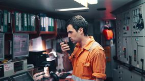 Marine Engineer, die an Funkverbindung an der Maschinen-Leitstelle arbeitet stock footage