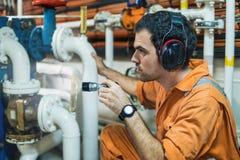 Marine engineer inspecting ship`s engine in engine control room. Marine engineer inspecting ship`s engine with torchlight in engine control room ECR. Seamen`s Stock Photo
