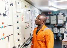 Marine engineer officer working in engine room. Marine engineer officer in engine control room ECR. Seamen`s work. He starts or stops main engine of ship stock photo