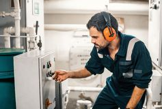 Marine engineer officer working in engine room royalty free stock photography