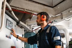 Marine engineer officer working in engine room royalty free stock images