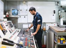 Marine engineer officer working in engine room. Marine engineer officer in engine control room ECR. Seamen`s work. He starts or stops main engine of ship royalty free stock images