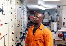 Marine engineer officer working in engine room. Marine engineer officer in engine control room ECR. Seamen`s work. He starts or stops main engine of ship stock images