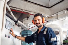 Marine engineer officer working in engine room. Marine engineer officer in engine control room ECR. Seamen`s work. He starts or stops main engine of ship royalty free stock photos