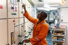 Marine engineer officer working in engine room. Marine engineer officer in engine control room ECR. Seamen`s work. He starts or stops main engine of ship royalty free stock image