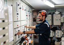 Marine engineer officer working in engine room. Marine engineer officer in engine control room ECR. Seamen`s work. He starts or stops main engine of ship stock photos