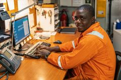 Marine engineer officer working in engine room. African marine engineer officer in engine control room ECR. Seamen`s work. He works at the computer stock images