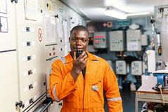 Marine engineer officer working in engine room. African marine engineer officer in engine control room ECR. He speaks with VHF or UHF portable radio. Ship royalty free stock photos