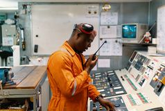 Marine engineer officer working in engine room. African marine engineer officer in engine control room ECR. He speaks with VHF or UHF portable radio. Ship royalty free stock images
