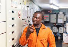Marine engineer officer working in engine room. African marine engineer officer in engine control room ECR. He speaks with VHF or UHF portable radio. Ship stock photography