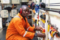 Marine engineer officer working in engine room. African marine engineer officer in engine control room ECR. He works in workshop and chooses correct tools and stock photography