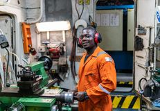 Marine engineer officer working in engine room. African marine engineer officer in engine control room ECR. He works in workshop with equipment stock photo