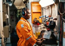 Marine engineer officer working in engine room. African marine engineer officer in engine control room ECR. He works in workshop with equipment stock images