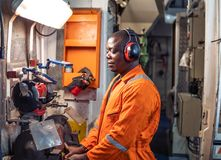 Marine engineer officer working in engine room. African marine engineer officer in engine control room ECR. He works in workshop with equipment stock image