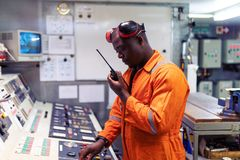 Marine engineer officer working in engine room. African marine engineer officer in engine control room ECR. He speaks with VHF or UHF portable radio. Ship royalty free stock image