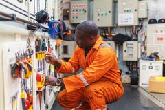 Marine engineer officer working in engine room. African marine engineer officer in engine control room ECR. He works in workshop and chooses correct tools and royalty free stock photography