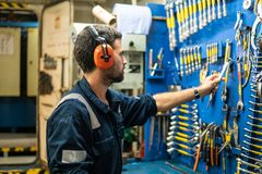 Marine engineer officer working in engine room. Caucasian marine engineer officer in engine control room ECR. He works in workshop and chooses correct tools and royalty free stock photo