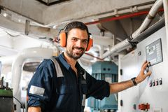 Marine engineer officer working in engine room. Marine engineer officer in engine control room ECR. Seamen`s work. He starts or stops main engine of ship royalty free stock photo